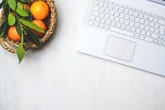 Vista superior colocada plano do lugar da mesa ou de trabalho com portátil e da cesta de laranjas frescas foto de stock