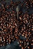 Vista superior com os feijões de café roasted no fundo escuro da tabela, espaço da cópia Imagens de Stock