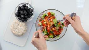 Vista superior Cozinhando o ponto baixo do vegetariano - salada grega da caloria, as mãos da mulher que lanç a salada da 4K vídeos de arquivo