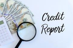 Vista superior da cédula da calculadora, da lupa e do dólar no fundo branco escrito com relatório de crédito imagens de stock