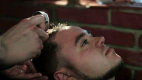 Vista superior da cara do homem que inclina sua cabeça de novo em um dissipador com olhos fechados quando barbeiro que lava seu c vídeos de arquivo