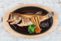 Vista superior da caranga fritada com rabanete, cenoura, shiitake e soma choy na placa quente na placa de madeira no papel japonê Imagens de Stock