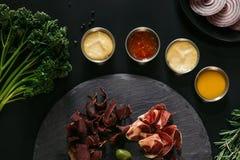 vista superior da carne gourmet do ofício com vários molhos no preto fotografia de stock