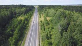 Vista superior da estrada no grampo da floresta Tráfego na estrada rural com a cidade no fundo no céu nebuloso imagem de stock