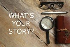Vista superior da lupa, do caderno, da pena, e dos vidros no fundo de madeira escrito com pergunta What& x27; s sua história imagens de stock royalty free