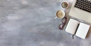 Vista superior da mesa de escritório no fundo textured cinzento Imagens de Stock