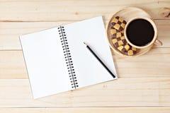 Vista superior da mesa de trabalho com o caderno vazio com lápis, cookies e copo de café no fundo de madeira Fotos de Stock Royalty Free