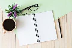 Vista superior da mesa de trabalho com o caderno vazio com lápis, copo de café, monóculos e planta no fundo de madeira Fotos de Stock