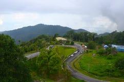 Vista superior da montanha de Gunung Raya à estrada e ao desportista prontos para a raça de corrida, ilha de Langkawi, Malásia foto de stock