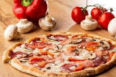 Vista superior da pizza deliciosa de Capricciosa na tabela de madeira Os ingredientes descascaram o tomate, queijo, presunto, cog imagem de stock royalty free