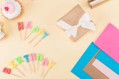 Vista superior da rotulação do feliz aniversario, do envelope com fita, dos bolos e de cartões coloridos no rosa Imagem de Stock Royalty Free
