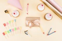 Vista superior da rotulação do feliz aniversario, do envelope com fita, dos bolos e de cartões coloridos no rosa Imagem de Stock