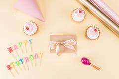 Vista superior da rotulação do feliz aniversario, do envelope com fita e de queques deliciosos no rosa Foto de Stock