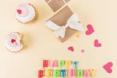 Vista superior da rotulação, dos bolos e da caixa de presente do feliz aniversario no bege Imagem de Stock Royalty Free