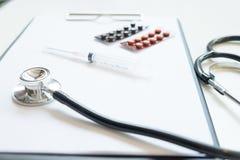 Vista superior da tabela da mesa do doutor com estetoscópio e bloco de notas com imagem de stock