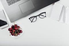 Vista superior da tabela do freelancer com portátil, caderno, telefone, vidros e petisco Comendo cerejas ao trabalhar workspace imagem de stock royalty free