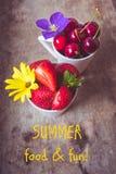 Vista superior das morangos, das cerejas e de flores amarelas e roxas em umas bacias no fundo, no alimento do verão e no divertim imagem de stock