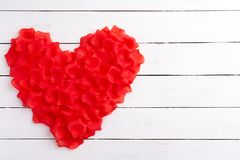 Vista superior das pétalas de rosas vermelhas na forma do coração no fundo de madeira branco fotografia de stock
