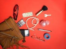 Vista superior de accesorios y del teléfono femeninos en un fondo rojo Fotografía de archivo libre de regalías