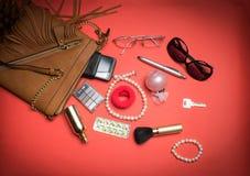Vista superior de accesorios y del teléfono femeninos en un fondo rojo Fotos de archivo