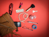 Vista superior de accesorios y del teléfono femeninos en un fondo rojo Fotos de archivo libres de regalías