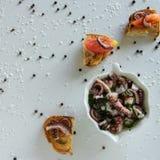 Vista superior de aperitivos italianos sabrosos - bruschetta con los tomates y los tentáculos crudos del pulpo, en rebanadas de b fotos de archivo