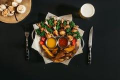 vista superior de batatas cozidas deliciosas com galinha, molhos e vidro roasted da cerveja fotos de stock