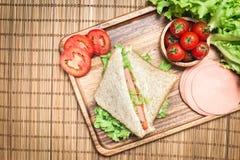 Vista superior de bocadillos y del jamón con los tomates, el bocadillo de club con queso y la verdura imagen de archivo