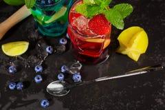 Vista superior de cócteles brillantes con la menta, el hielo, las bayas y el carambola en el fondo de madera Bebidas del verano C Foto de archivo