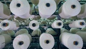 Vista superior de carretes de giro con los hilos blancos Equipo de producción de la fábrica de la ropa almacen de metraje de vídeo