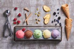 Vista superior de cinco bolas del helado del colorfull con los pistachos, plátano fotos de archivo