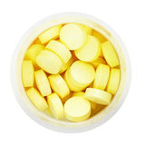 Vista superior de comprimidos amarelos na garrafa plástica redonda Imagem de Stock Royalty Free