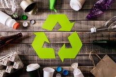 Vista superior de diversos materiales de la basura con el reciclaje de símbolo en fondo de la tabla Recicle, ambiente y concepto  imágenes de archivo libres de regalías