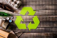 Vista superior de diversos materiales de la basura con el reciclaje de s?mbolo en fondo de la tabla o imágenes de archivo libres de regalías