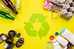 Vista superior de diversos materiales de la basura con el reciclaje de s?mbolo en fondo de la tabla o foto de archivo libre de regalías