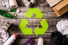 Vista superior de diversos materiales de la basura con el reciclaje de s?mbolo en fondo de la tabla Recicle, ambiente y concepto  imagen de archivo