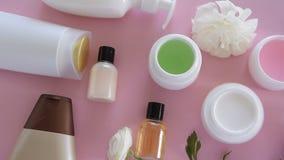 Vista superior de diversos productos y de flores higiénicos/cosméticos en fondo rosado fresco Tratamiento de la belleza de la s almacen de video