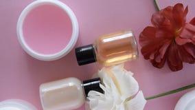 Vista superior de diversos productos y de flores higiénicos/cosméticos en fondo rosado fresco Tratamiento de la belleza de la s almacen de metraje de vídeo