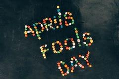 vista superior de doces arranjados na rotulação do dia de tolos de abril isolada no tabletop preto imagem de stock royalty free
