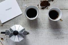 A vista superior de dois copos de café, o fabricante-moka italiano do café e o cartão branco com ` feliz do ` text Foto de Stock Royalty Free