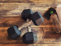 Vista superior de dos pesas de gimnasia de acero brillantes, del smartphone, de la botella de agua y de la toalla blanca en piso  Foto de archivo libre de regalías