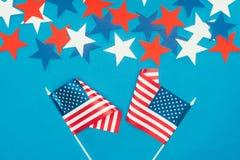 Vista superior de estrelas arranjadas e das bandeiras americanas isoladas no azul Imagens de Stock Royalty Free