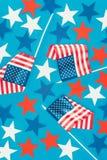 Vista superior de estrelas arranjadas e das bandeiras americanas isoladas no azul Fotos de Stock