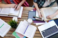 Vista superior de estudiantes jovenes con los libros y de notas en café Fotos de archivo libres de regalías