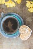 Vista superior de flores amarillas, de la taza de café azul y de una galleta del pan de jengibre en viejo fondo rústico de madera Foto de archivo libre de regalías