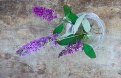 Vista superior de flores púrpuras en un florero de cristal en fondo de madera fotografía de archivo