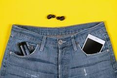 Vista superior de fones de ouvido, de calças de brim, do carregador e do smartphone sem fio em seu bolso no fundo amarelo fotografia de stock