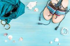 Vista superior de gafas de sol, de sandalias, de la bufanda y de las cáscaras del mar Foto de archivo libre de regalías