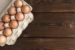 Vista superior de huevos frescos en la bandeja del papel en el contexto oscuro fotos de archivo libres de regalías