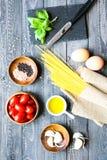 Vista superior de ingredientes italianos para o tomate e os espaguetes basílicos Fotografia de Stock